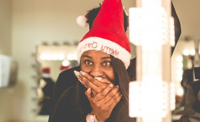 Woman with a Christmas hat covering her mouth